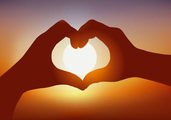 Concept de la déclaration d'amour avec deux mains qui forment un cœur devant un coucher de soleil