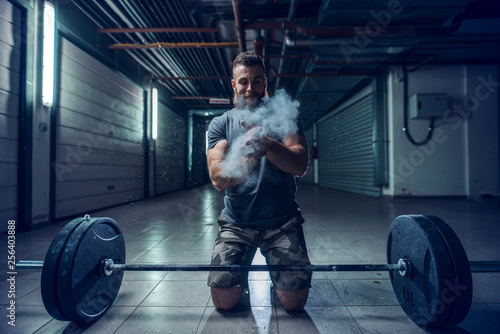 Strong muscular Caucasian bodybuilder clapping hands and