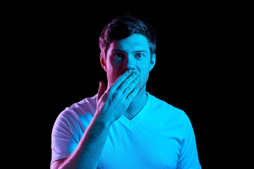 emotion, expression and people concept - portrait of young man in t-shirt covering his mouth by hand over ultra violet neon lights in dark room