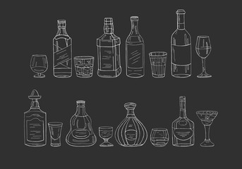Vintage alcohol bottles and glasses on black background