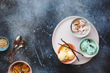 Colorful ice cream in colored bowls with spoons on rustic wooden background , blank space