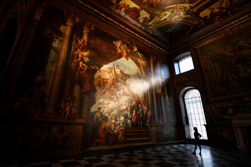 A gallery assistant poses beside a fresco during the reopening of The Painted Hall, Old Royal Navy College in London