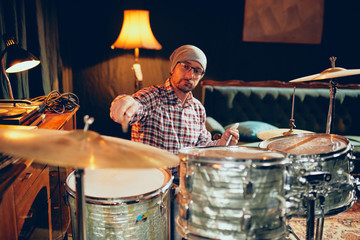 Caucasian drummer playing his instrument while sitting in home studio.