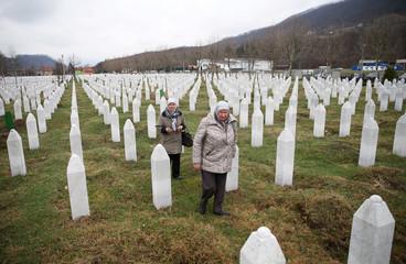 Women walk near a grave in the Memorial centre Potocari, near Srebrenica