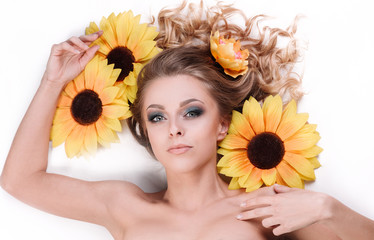 beautiful young woman lying among the flowers of a sunflower