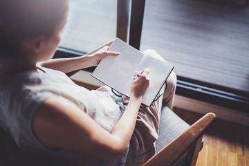 Working at home concept. Young business woman writing and taking notes while relax sitting in comfort chair at home. Preparing plans for next week.