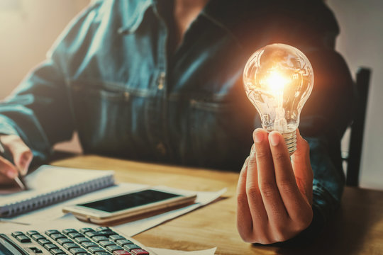 business woman hand holding light bulb in office. conept saving energy