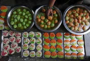 Sweets featuring election symbol of different Indian political parties are pictured inside a sweets making workshop on the outskirts of Kolkata