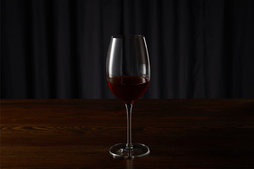 Glass with red wine on wooden surface on dark