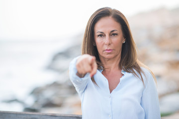 Beautiful middle age hispanic woman at the sea shore on a sunny day pointing with finger to the camera and to you, hand sign, positive and confident gesture from the front