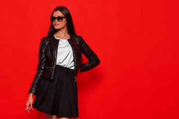 Young fashion woman in black leather jacket and black skirt. Red background studio shot