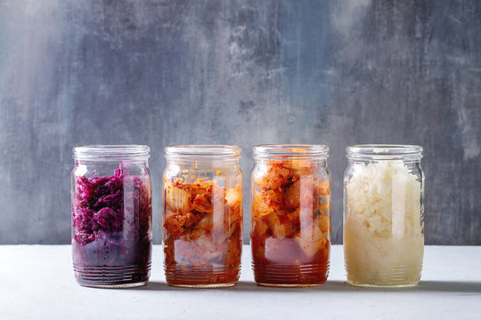 Variety of fermented food korean traditional kimchi cabbage and radish salad, white and red sauerkraut in glass jars in row over grey blue table.