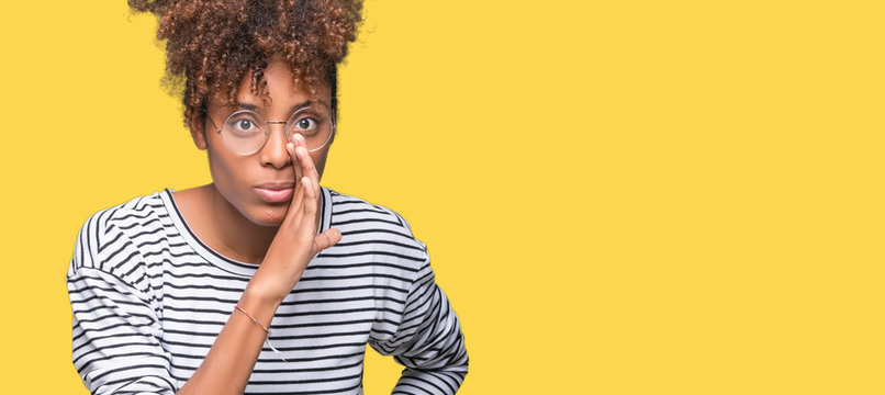 Beautiful young african american woman wearing glasses over isolated background hand on mouth telling secret rumor, whispering malicious talk conversation
