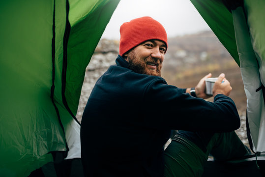 Portrait of a view from tent entrance of young traveler man smiling and relaxing in mountains near to bonfire. Rear view of hiker male sitting in the camping tent, drinking hot beverage. Travel people