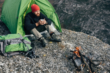 Overhead otdoors shot of young explorer man drinking hot beverage in mountains, sitting near to bonfire, relaxing after trekking. Traveler man in red hat holding a mug of tea after hiking. Travel