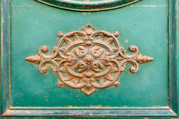 rusty ornamental decoration at a green door in Italy