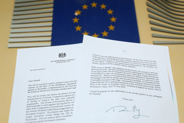 A copy of the letter sent by British Prime Minister Theresa May to European Council President Donald Tusk is seen next to an European Flag in this illustration picture