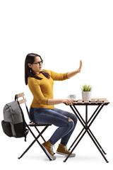 Angry female student in a cafe sitting at a table with coffee and gesturing stop with hand