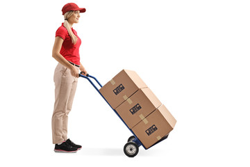 Female worker standing with boxes on a hand truck