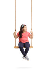 Little girl sitting on a swing and looking to the side