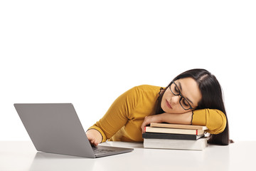 Tired female student lying on a pile of books and working on a laptop computer
