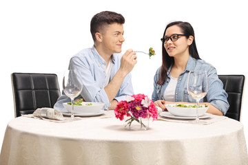 Young boyfriend giving a salad to his girlfriend at a restaurant table