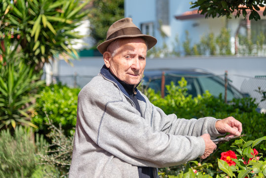 Happy mature retired man cleaning his garden wearing hat