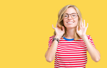 Beautiful young woman wearing glasses over isolated background Trying to hear both hands on ear gesture, curious for gossip. Hearing problem, deaf