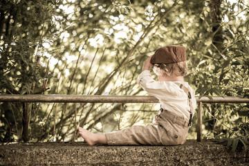 Junge sitzt auf der Mauer