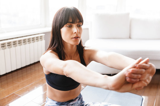 Portrait of beautiful woman stretching her body while doing sports or yoga on mat at home