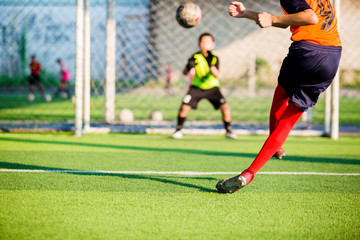 soccer player run to shoot ball at penalty kick to goal with blurry goalkeeper background, concept of making goals and protection
