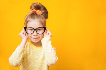 Cute child girl with glasses on a yellow background. Correction of vision in childhood
