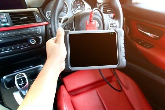 Mechanic is using a car diagnostic tools servicing a car. Blank screen of car diagnostic tools using in red interior car.
