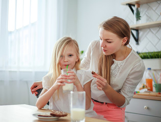 Mother and child daughter in home kitchen having fun drinking milk, healthy family lifestyle