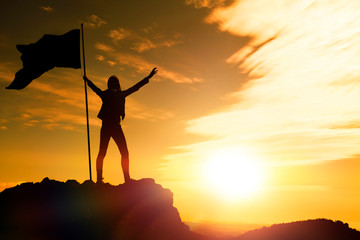 girl with a flag on top of the mountain against the evening sky. the achievement of the objectives, tourism, travel.