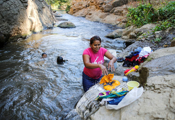 A woman washes clothes at the El Salto waterfall in San Rafael del Sur