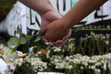 Students and residents take part in a symbolic hug during a tribute and an ecumenic ceremony to commemorate victims of the shooting at the Raul Brasil school in Suzano