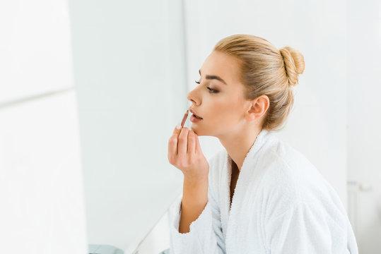 beautiful and blonde woman in white bathrobe applying lip liner in bathroom