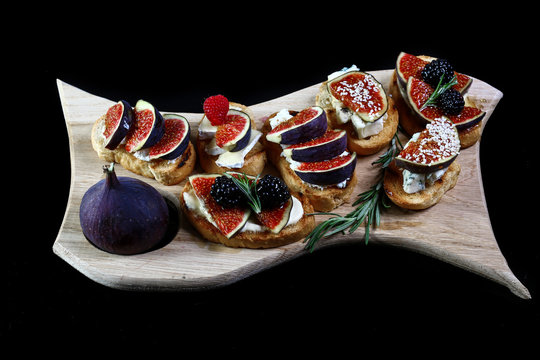 Making dinner with low carbs ingredients for healthy eating concept and weight loss. Appetizer of figs and brie cheese with honey. Sandwiches with figs