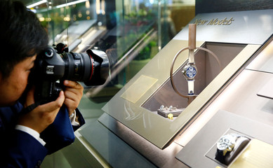 A visitor takes a picture of a watch at the exhibition stand of Swiss watch manufacturer Patek Philippe at the Baselworld watch and jewellery fair in Basel