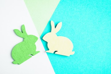 Yellow and green wooden Easter bunny on colored geometric background. Trendy creative photo. Minimal concept