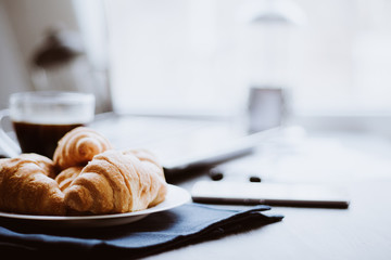Macro shot of Smartphone and Laptop fresh croissants and coffee black background. Mate moody color. concept of work.