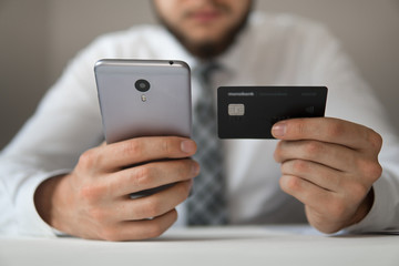 Businessman uses credit card and a smartphone. Online payment. Close up telephone. Mobile phone. Office work concept. Shopping online.