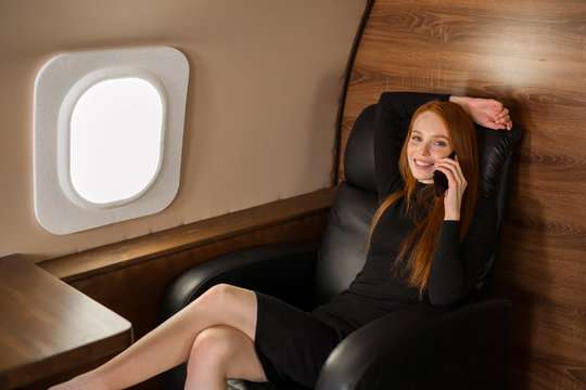 beautiful young girl with red hair talking on the phone in the cabin of a private jet