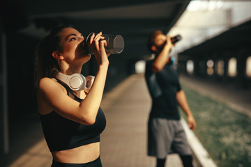 Young woman and man drinking protein shake after workout