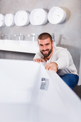 Man buyer choosing ceramic bath  in bathroom furniture shop