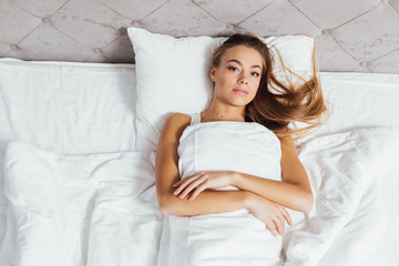 beautiful young girl in bed in a very soft mattress