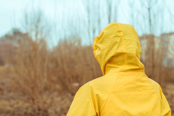 Rear view of woman in raincoat looking into distance