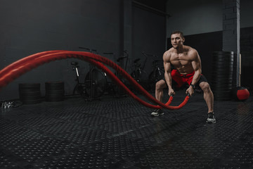 Man wear red shorts doing battle ropes exercise at the crossfit gym