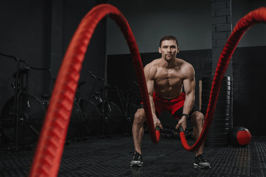 Muscular man doing battle ropes exercise at the crossfit gym